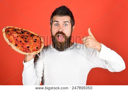 Handsome Surprised Bearded Man With Pizza. Happy Hungry Man Eating Pizza And Showing Thumbs Up Gestu