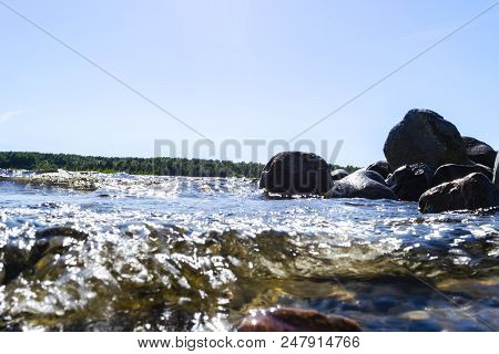 Big Windy Waves Splashing Over Rocks. Wave Splash In The Lake Against Beach. Waves Breaking On A Sto