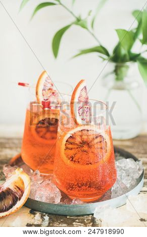 Italian Aperol Spritz Alcohol Cocktail With Ice And Blood Orange Slices On Table, Vertical Compositi