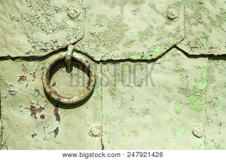Architecture Metal Background. Old Light Metal Door With Rivets And Aged Metal Door Handle In The Fo