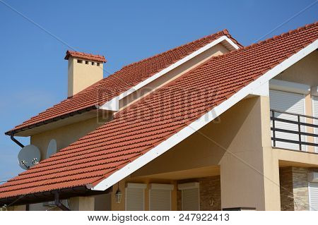 House With Clay Tile Roof, Rain Gutter, Chimney, Gable And Valley Type Of Roof Construction. Buildin
