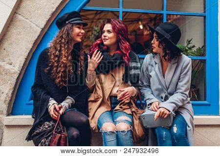 Outdoor Shot Of Three Young Women Chatting And Laughing On City Street. Best Friends Talking And Hav