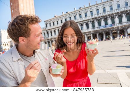 Happy couple laughing eating ice cream on vacation travel in Venice, Italy. Smiling happy young couple in love having fun eating italian gelato food on San Marco Square, Venice, Italy holidays.