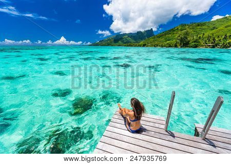 Bora bora luxury travel overwater bungalow resort vacation bikini woman at Tahiti hotel. Tropical exotic destination. Girl relaxing sitting on private balcony under the sun looking at ocean.