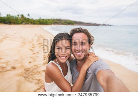 Two friends taking self portrait picture with phone. Smiling young interracial couple taking selfie on vacation travel. Asian woman, Caucasian man. Two young adults happy.