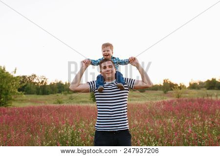 Small Boy Sitting On His Fathers Shoulders And Holding Hands In The Field During Beautiful Sunset.