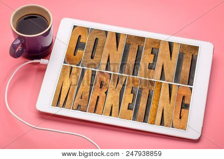 content marketing  - word abstract in vintage  letterpress wood type printing blocks on a digital tablet with a cup of coffee