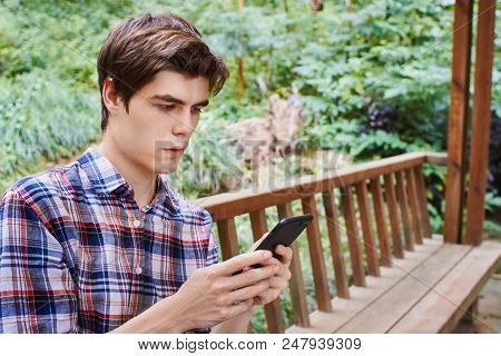Young Man Wearing Colorful Shirt Is Sitting In The Wooden Summerhouse And Looking At The Cellphone A