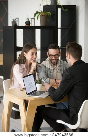 Architect Or Designer Discussing House Plan With Excited Millennial Buyers Couple Visiting His Offic