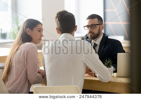 Serious Broker Or Realtor Listening To Millennial Couple Arguments Or Ideas During Office Meeting, I