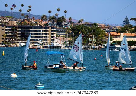 July 2, 2018 In Newport Beach, Ca:  People Sailing In Small Sail Boats Called Dinghy Boats Taken In