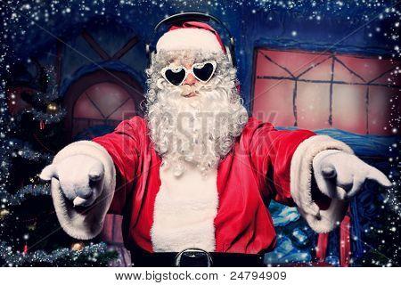 Santa Claus is listening to music in headphones. Christmas.