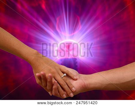 Engagement hands with electronic Plasma Ball. A couple hold hands with a wedding ring against a Plasma Ball background.