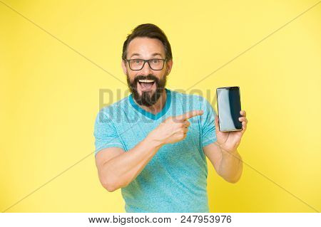 Check Out New App. Guy Eyeglasses Cheerful Pointing At Smartphone. Man Happy User Recommends Try App