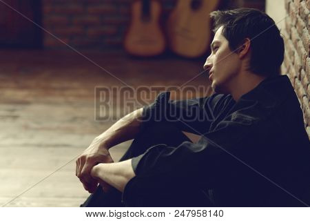 Portrait of a sad, pensive young man. Loft style interior. Men's beauty.