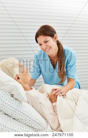 Nurse cares for a sick elderly woman in the hospice or at home