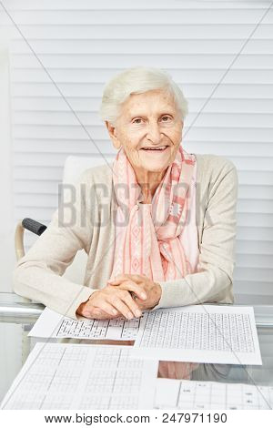 Old woman solves puzzles as a memory training in the retirement home or at home