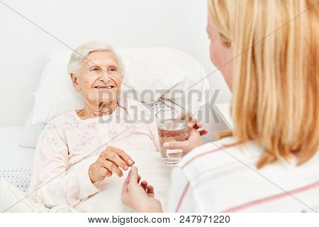 Sick elderly woman lies in bed and takes a medicine with water