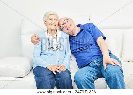 Happy seniors couple is sitting on the sofa at home or in a retirement home
