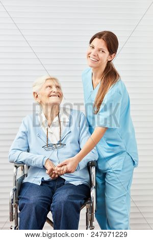 Young woman as a geriatric nurse and a senior citizen in a wheelchair at the retirement home