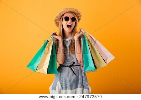 Portrait of a happy young blonde woman in summer hat and sunglasses holding shopping bags isolated over yellow background