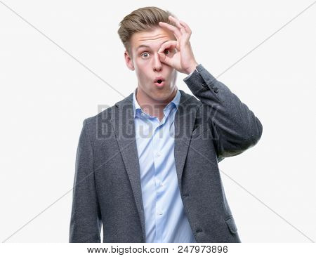 Young handsome blond business man doing ok gesture shocked with surprised face, eye looking through fingers. Unbelieving expression.