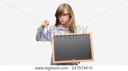 Young blonde child holding blackboard with angry face, negative sign showing dislike with thumbs down, rejection concept poster