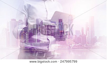 double exposure image of a business man using a tablet device during sunrise overlay with cityscape image. modern life and business concept