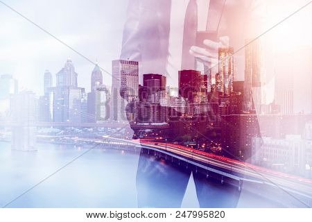 double exposure image of a business man using a smartphone device during sunset overlay with cityscape image. modern life and business concept