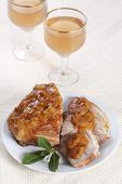 Roasted pork with apricot sauce on a plate and two glasses of wine poster