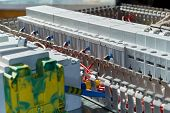 Modern modular contactors and circuit breakers with electrical wires connected to them. Assembly of the electric Cabinet in the workplace. The wires are laid in perforated cable channels. poster