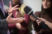 The correspondent interviews.Microphone and hands. Interviewer and respondent. The reporter is interviewing poster