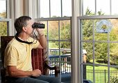 Senior man watching chickadee bird on birdfeeder through binoculars from chair poster