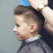 Barber shop. Barber makes hairstyle to a boy with styling gel and hairbrush. poster