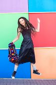 Cheerful beautiful slim girl with dreadlocks, rastaman, in a black dress and sneakers, jumps against the backdrop of a multi-colored wall, holding a rasta backpack. poster