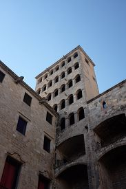 Old Tower In Barcelona (catalonia, Spain) Against Blue Sky In Summer. Striking Dark-light Contrast.