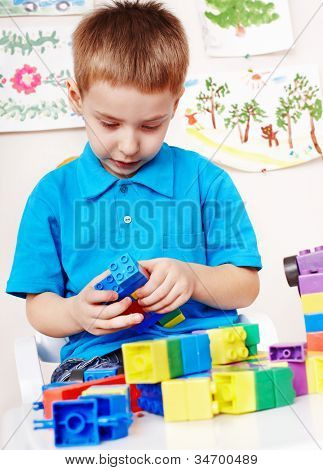 Little boy playing construction set.