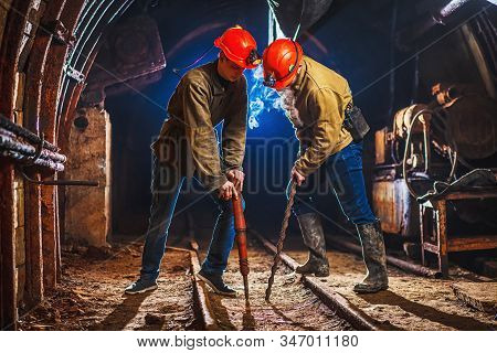 Two Miners In The Mine. Two Young Guys In A Working Uniform And Protective Helmets
