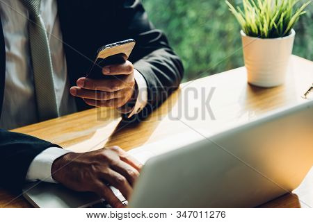 Business Man Working On Mobile Smart Phone With Laptop Computer On Desk Home Office