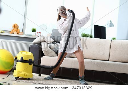 Portrait Of Young Female Having Fun And Singing In Vacuum Cleaners Tube In Living Room. Beautiful Wo