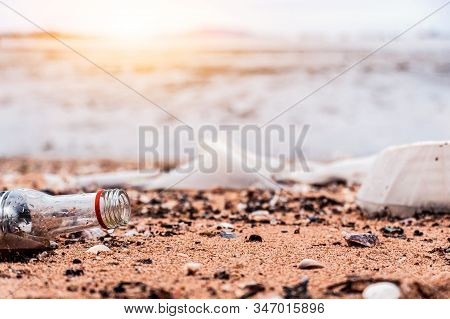 Plastic Glasses And Garbage On The Sandy Beach. Environmental & Plastic Awareness. World Environment