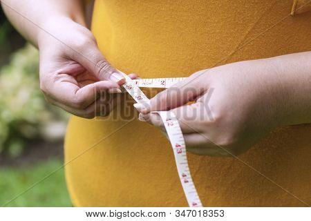 Hand Fat Woman Holding Measuring Tape Around Her Waist. Overweight Female Measuring Her Waist With M