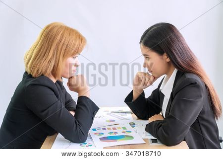 Two Confident Businesswomen Hold Hands On Chin While Sitting At Office Desk With Documents Looking A