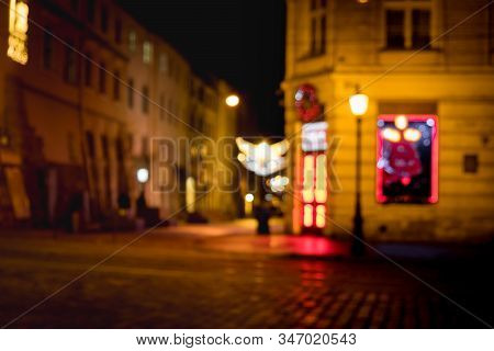 Out Of Focus Image Of Old European City Night Street. Night Street Neon Lights