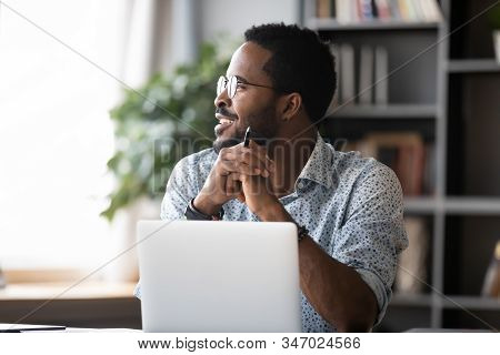 Smiling African Business Man Look Away Dreaming Working On Laptop