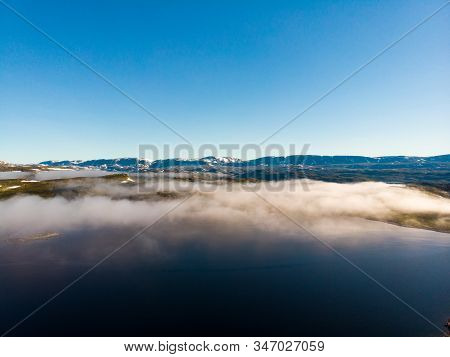 Aerial View. Norway Landscape. Morning Time, Clouds Over Lake Water And Snowy Mountains In Distance.