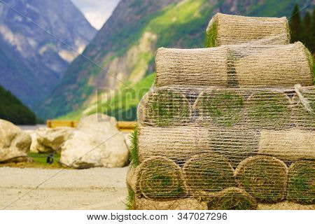 Stacks Of Sod Rolls For New Lawn. Natural Grass Turf For Installing Making New Field. Mountains Fjor
