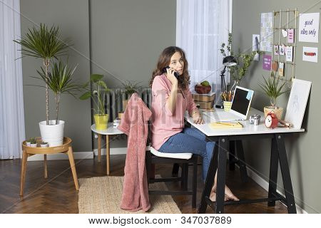 Woman Working From Home, Sitting On The Chair And Using Phone. Freelance Working