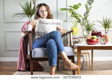Young Woman Sitting By A Living Room And Reading A Newspapers. There Are Some Houseplants On The Tab