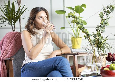 Young Woman Drinking Water Sitting On Armchair At Home. Health Benefits Of Drinking Enough Water Con